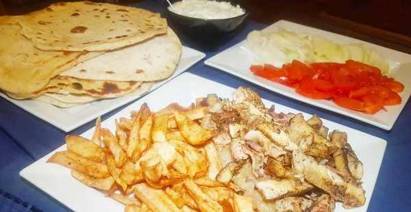 ingredients for souvlaki - pork, deep fried potato, tomato, onion, tzatziki, pita